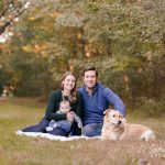 Family sitting on blanket in the fall with dog and baby.