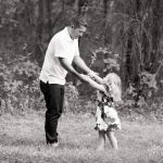 Dad dancing with little girl in front of trees in the grass.