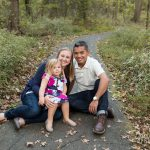 Family sitting on a paved trail in front of trees with white wildflowers.