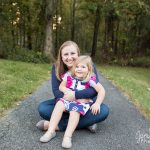 Mother and daughter sitting on a paved trail in front of trees.