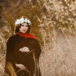 Maternity photo of asian woman wearing floral crown and floor length black winter coat with red accents.