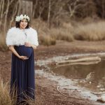 Maternity photo of asian woman wearing floral crown and floor length blue grown with faux fur shawl.