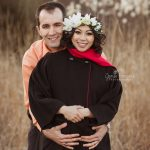 Maternity photo of couple, woman wearing long black coat with red accents.