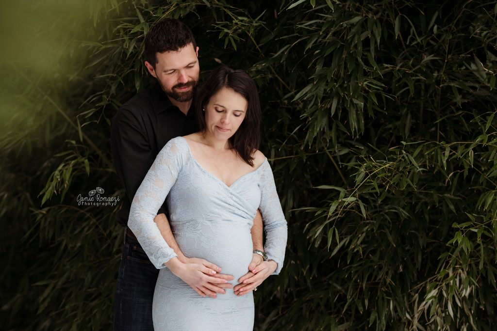 Photo of couple in front of bamboo. Maternity photo.
