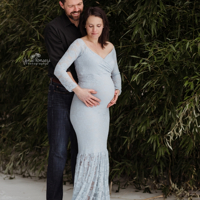 Photo of couple in front of bamboo. Maternity photo in snow.