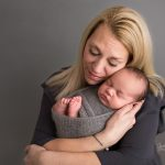 Newborn parent portrait on gray backdrop