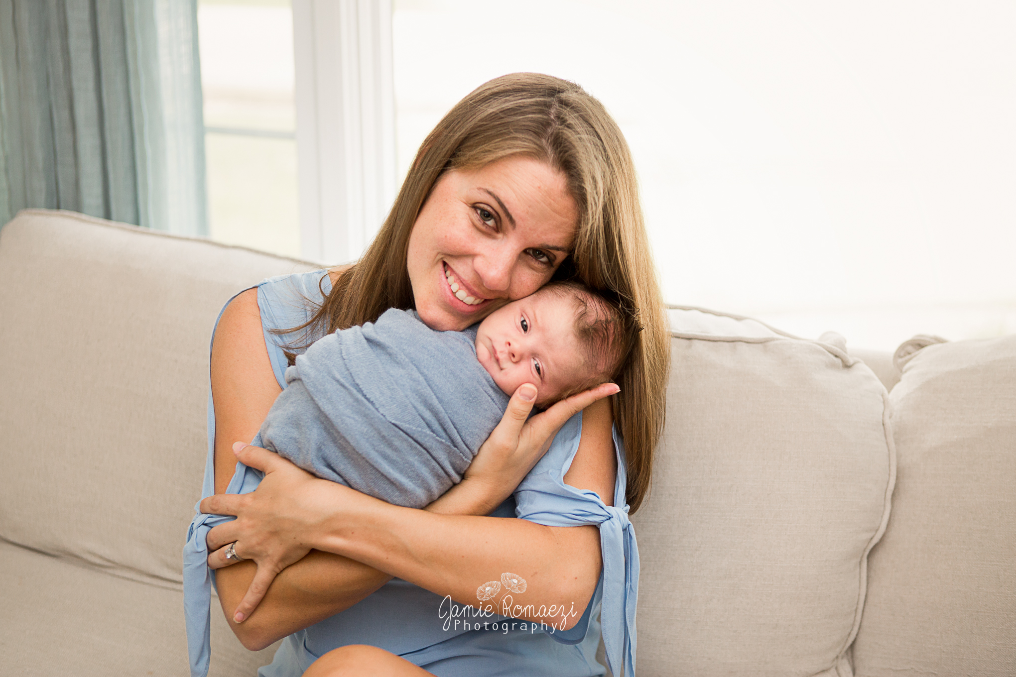 Mom sitting on couch posing with newborn in arms.