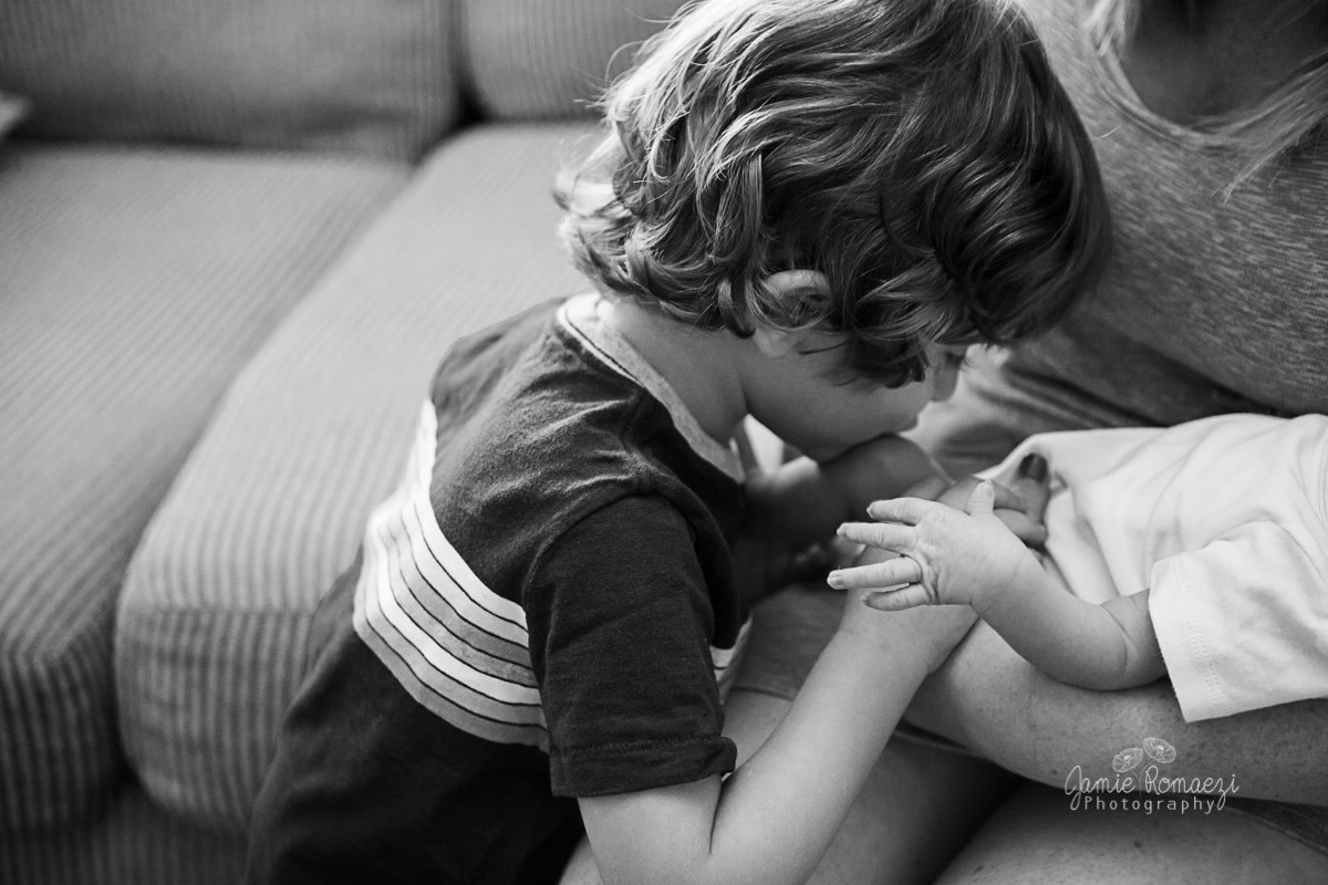 3 year old brother kissing baby toes with baby's hand in foreground. Black and white photo.