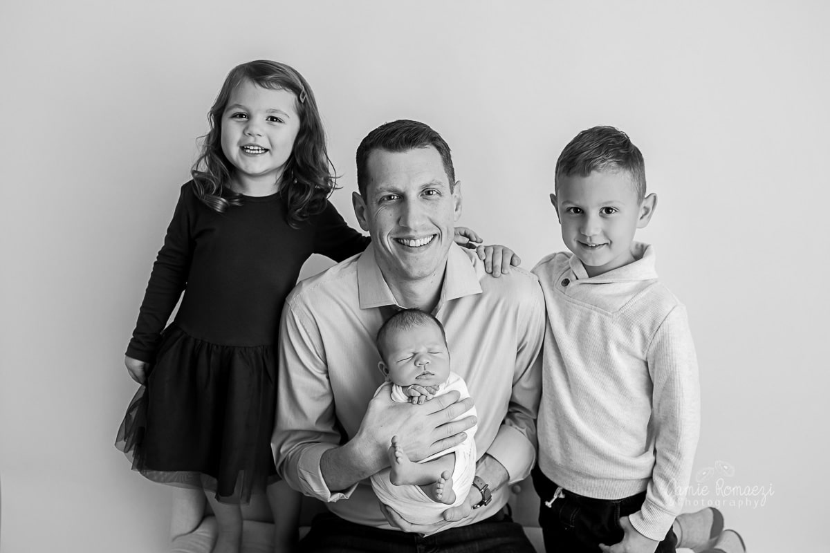 black and white photo of dad holding newborn baby while older kids stand next to him smiling.