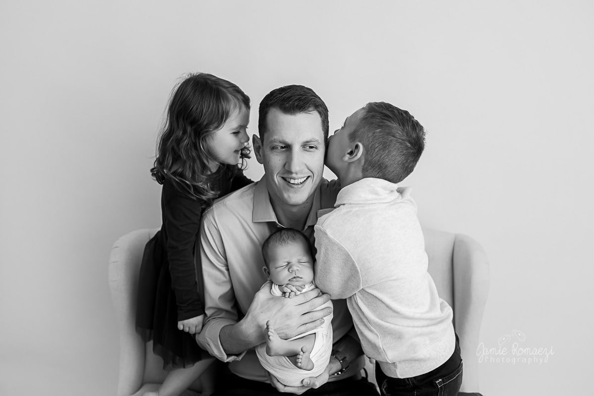 Photo of dad and all three kids in black and white while kids whisper in dad's ears.