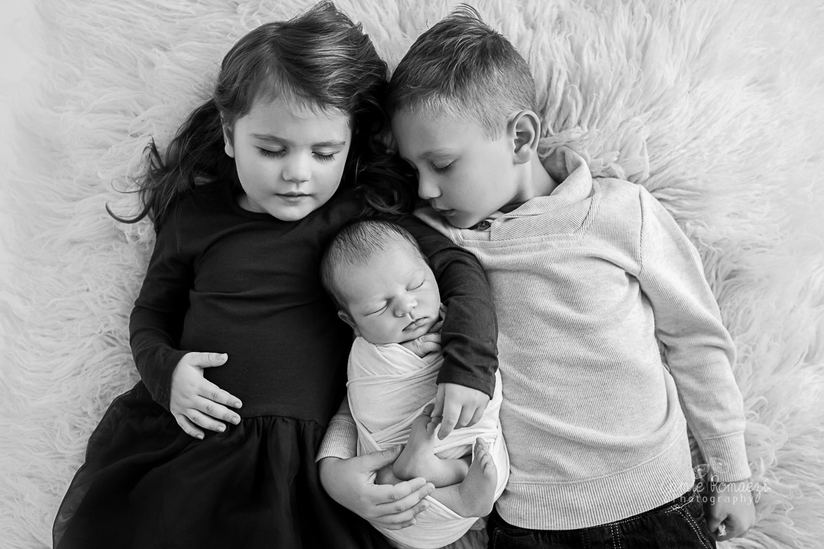 big brother and sister lying on their back with their eyes closed holding their baby brother, black and white image.