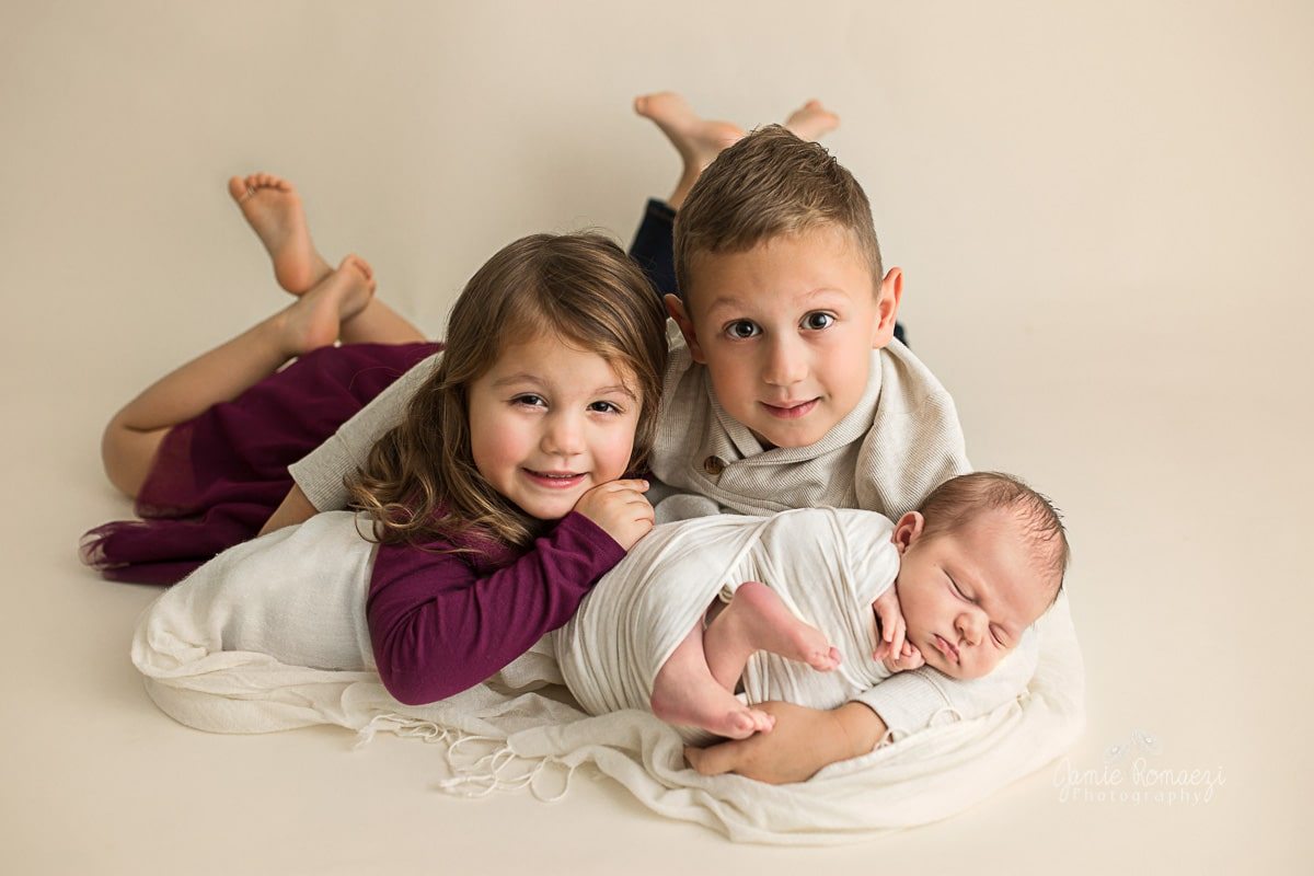 Big brother and sister lying on their stomach holding baby brother for photos.