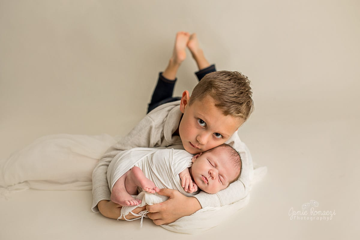 big brother lying on stomach holding baby brother for newborn photos.