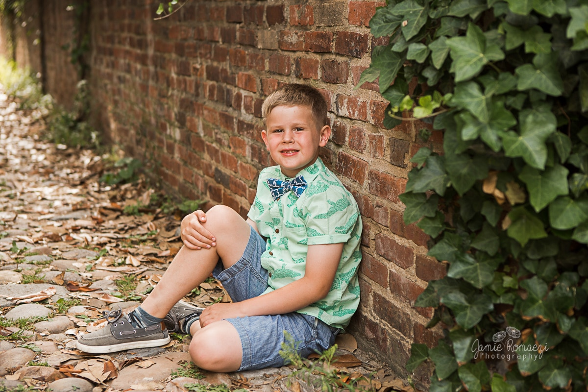 little boy leaning against a brick wall with english ivy