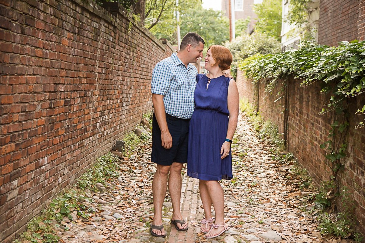 husband and wife nose to nose in a brick and cobblestone alleyway