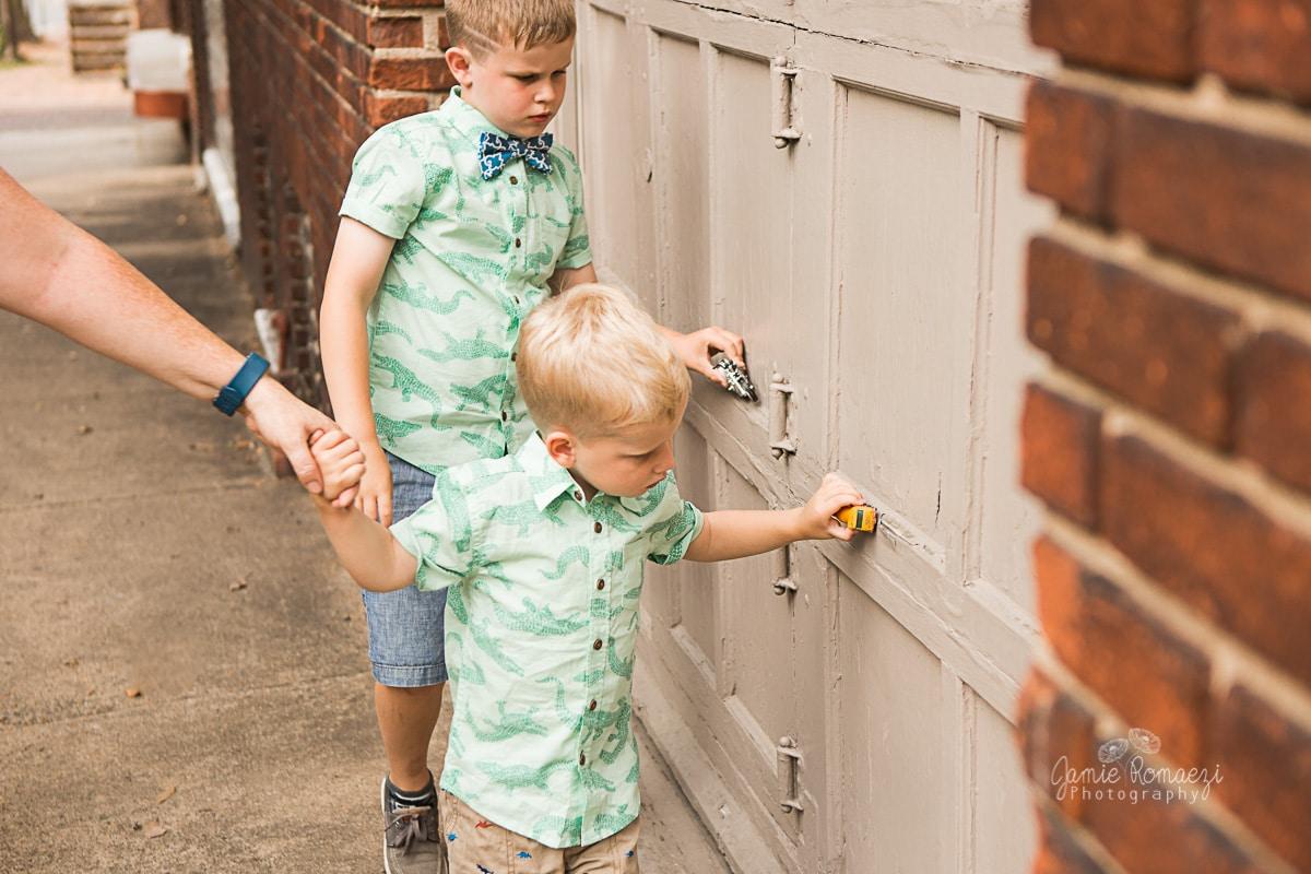 boys driving their matchbox cars along a garage door.