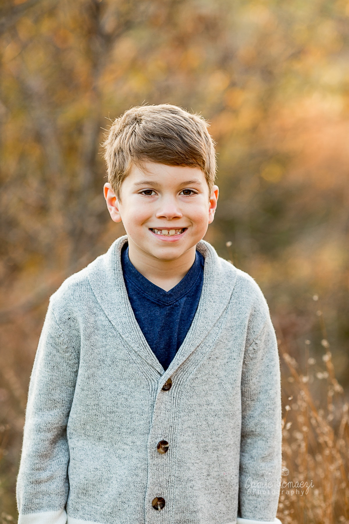 photo of 9 year old little boy smiling outdoors for fall photos