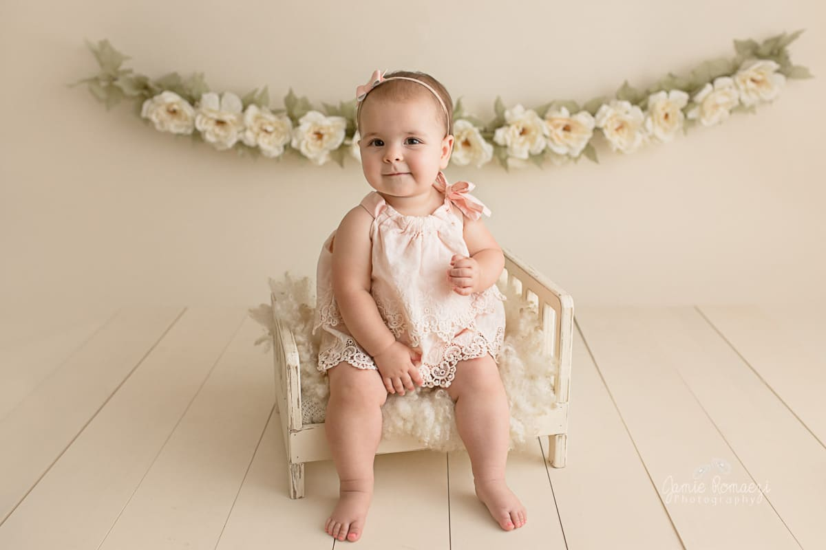 Photo of a 1 year old on cream backdrop with wood floor. Toddler is sitting on a tiny cream bed wearing a pastel pink romper with a flower garland in the background.