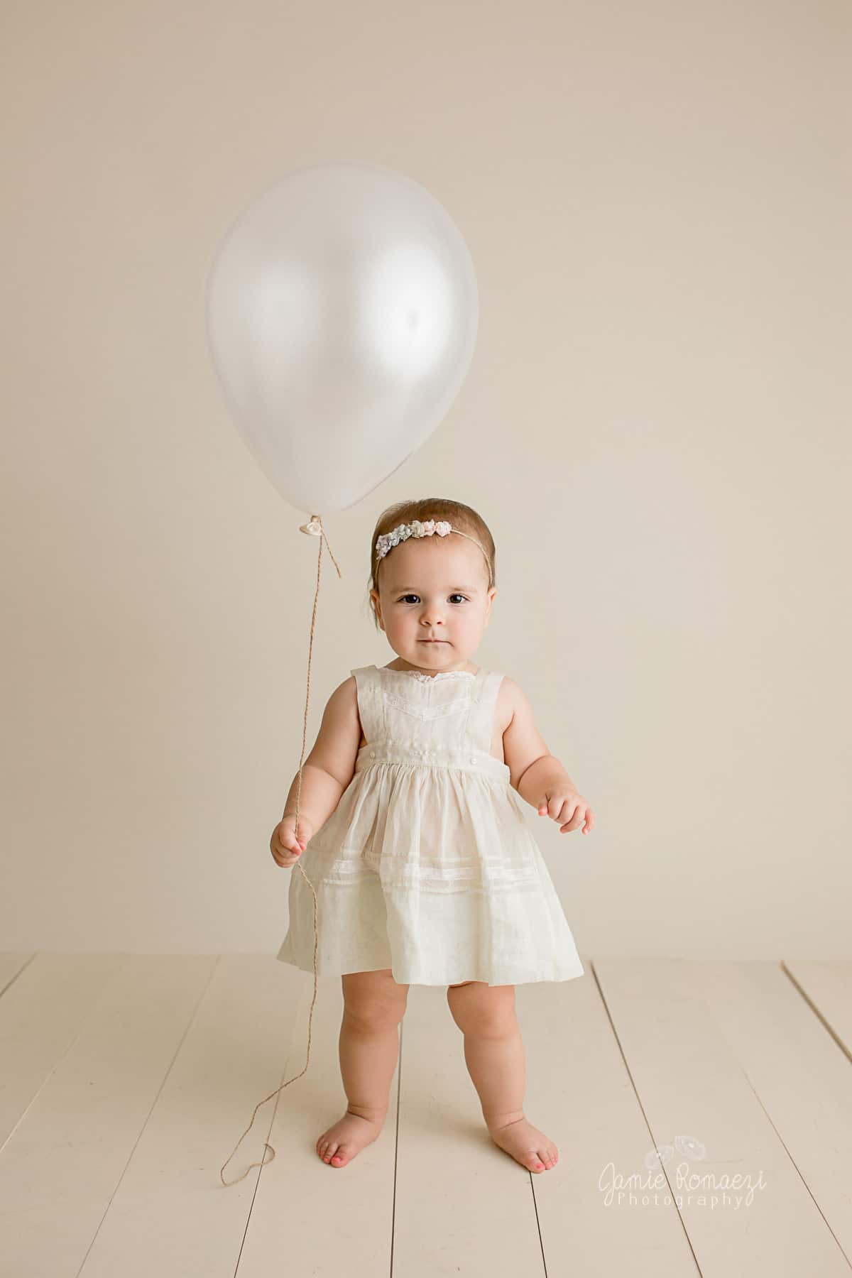 standing holding a cream colored balloon with twine for string.