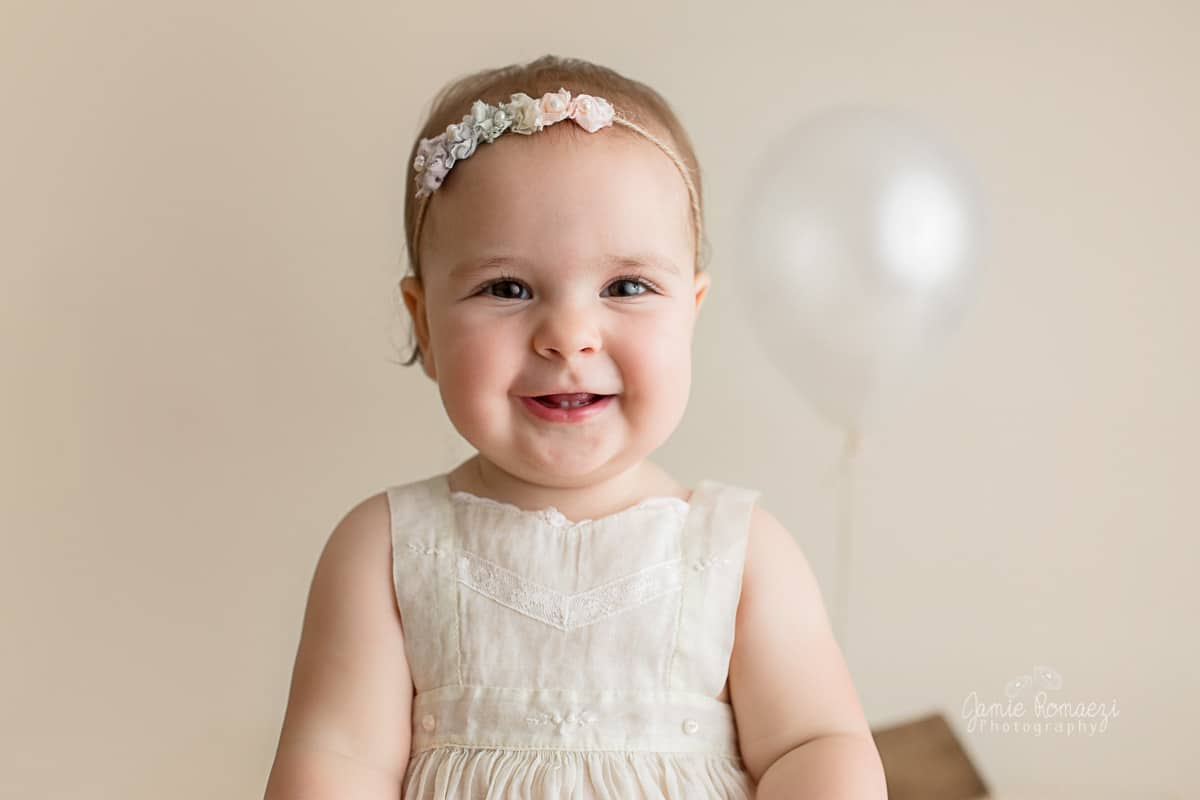 First birthday photo with cream balloon. Close up of smiling toddler face