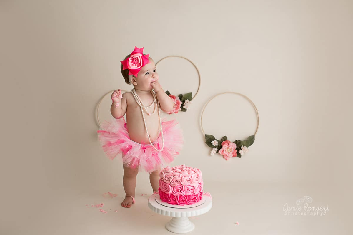 First birthday cake smash with pink gradiant cake and light pink floral hoops. Toddler is standing wearing a pink tutu, eating her cake.