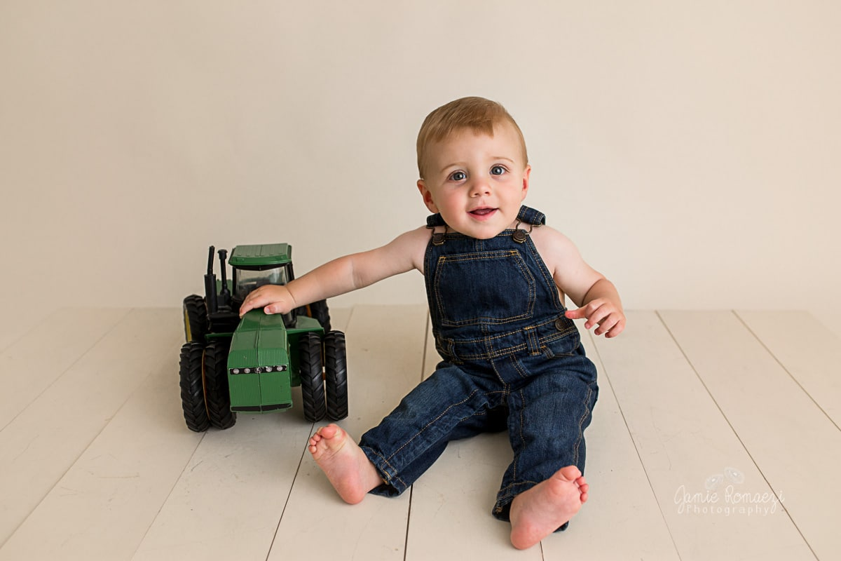 Smiling baby in overalls with antique tractor toy.