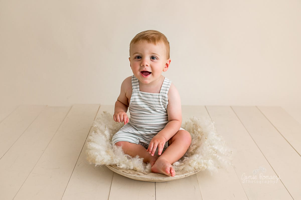 One year old in sage and cream striped romper sitting in a low bowl.