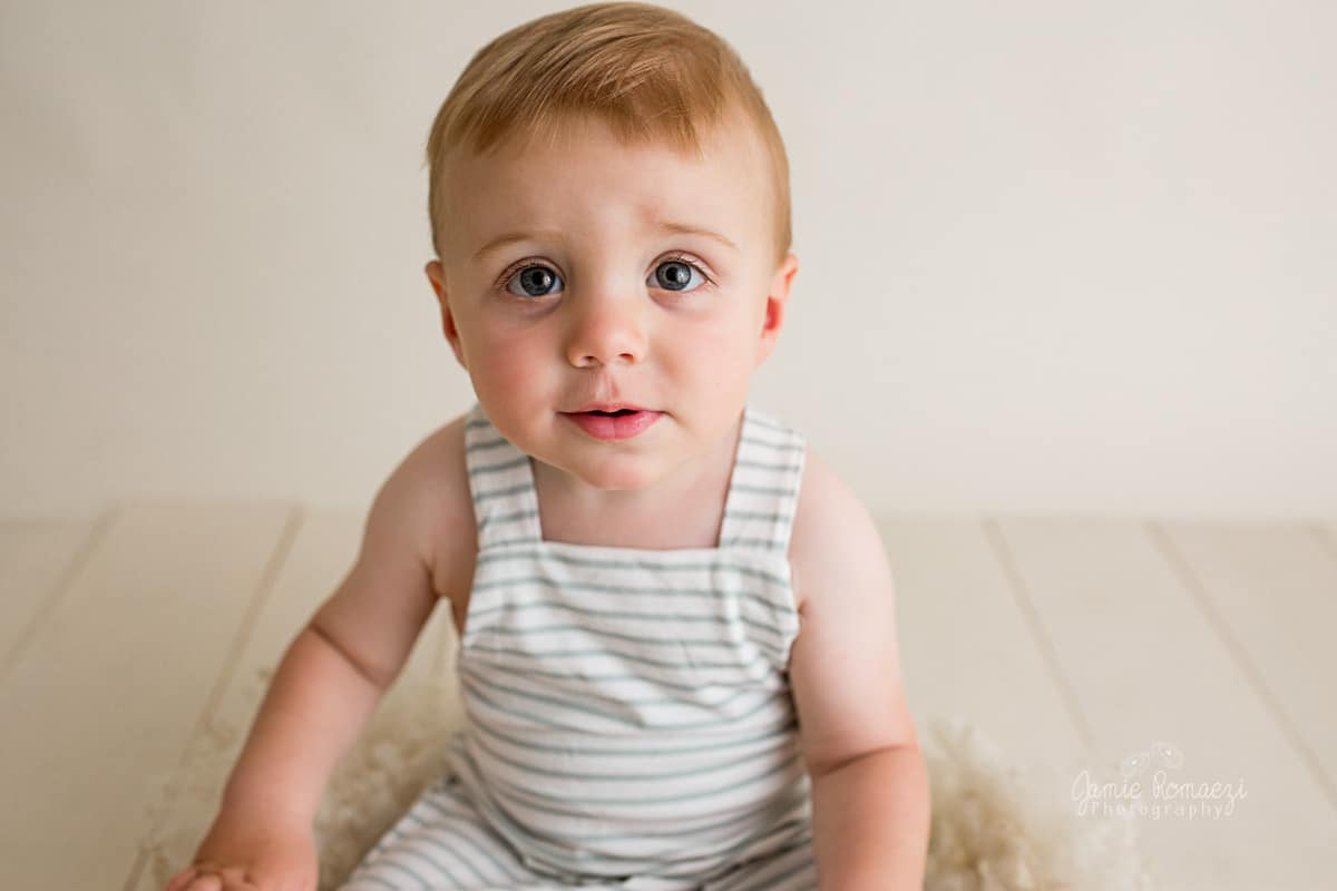 One year old boy sitting in a low bowl looking at the camera