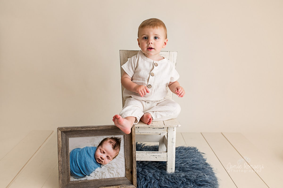 One year old sitting in a chair next to a framed photo of himself as a newborn.