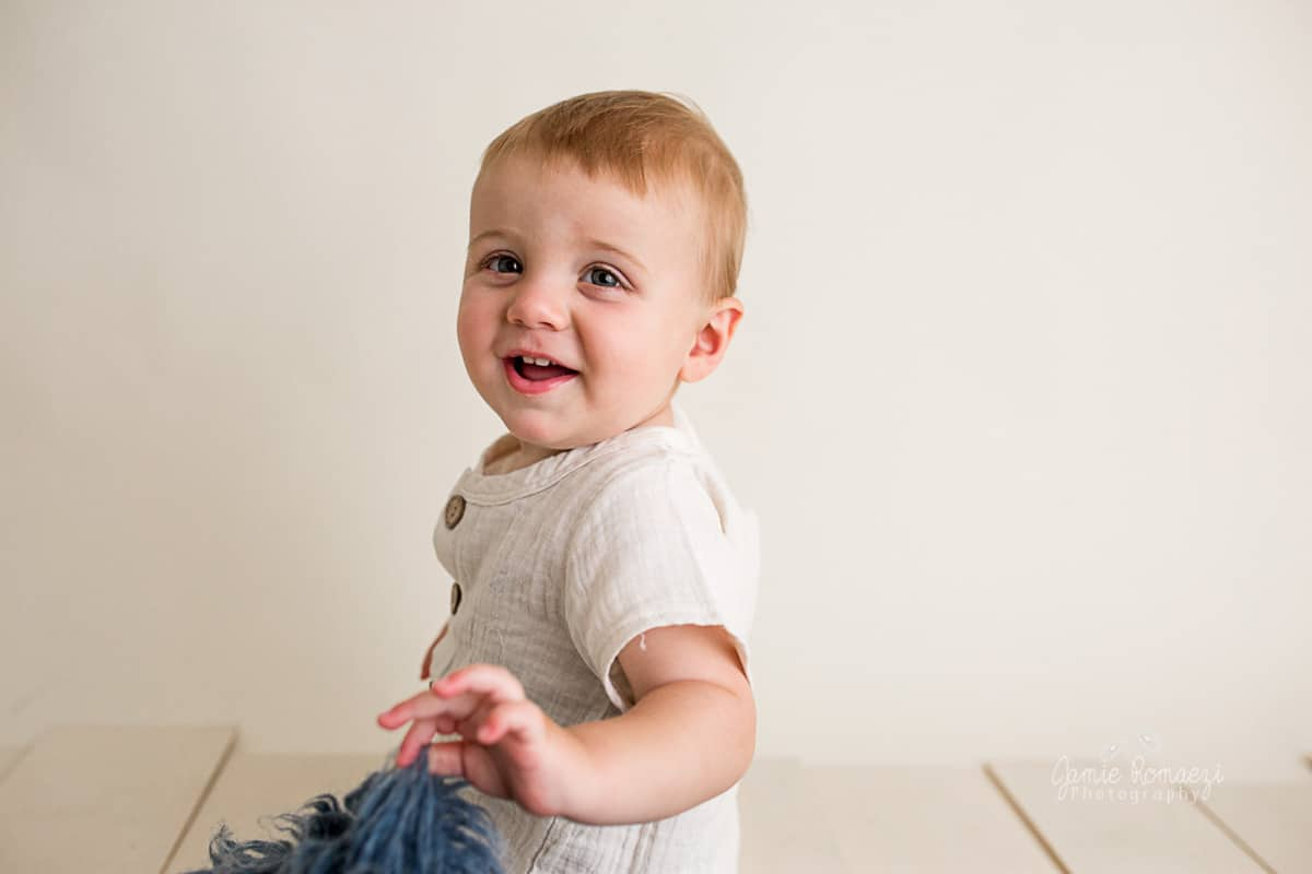 One year old smiling at the camera, studio portrait.
