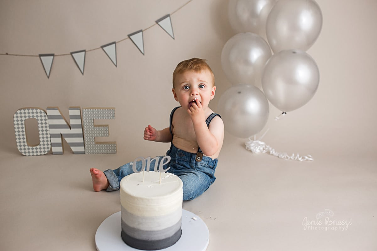 baby eating cake in front of gray ombre themed cake smash set.