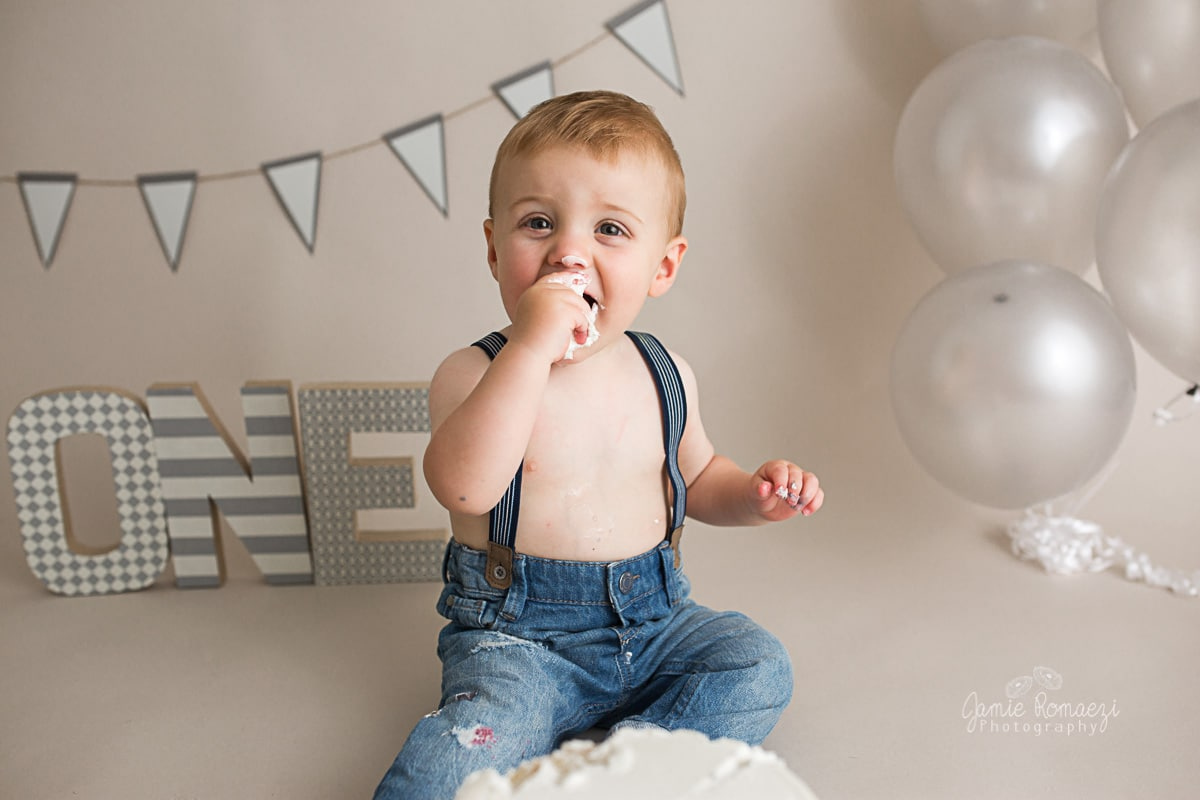 close up baby eating cake in front of gray ombre themed cake smash set.