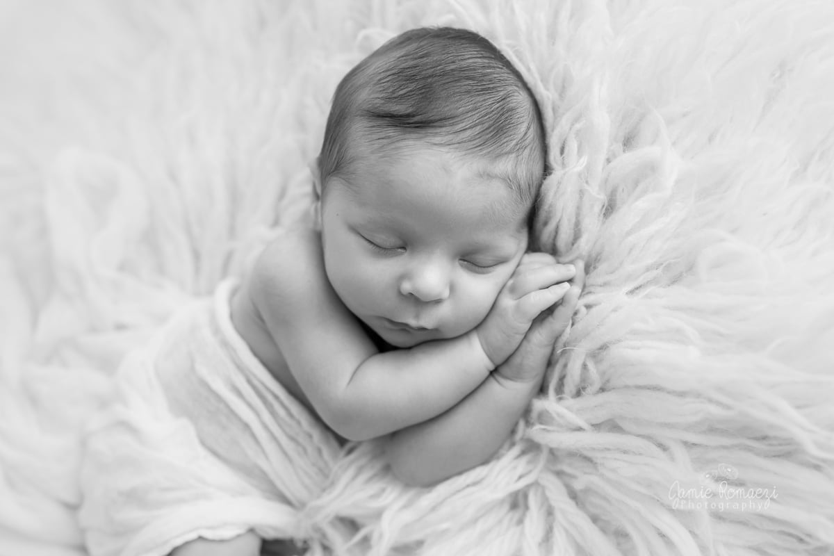 Black and white photo of baby boy laying on side.