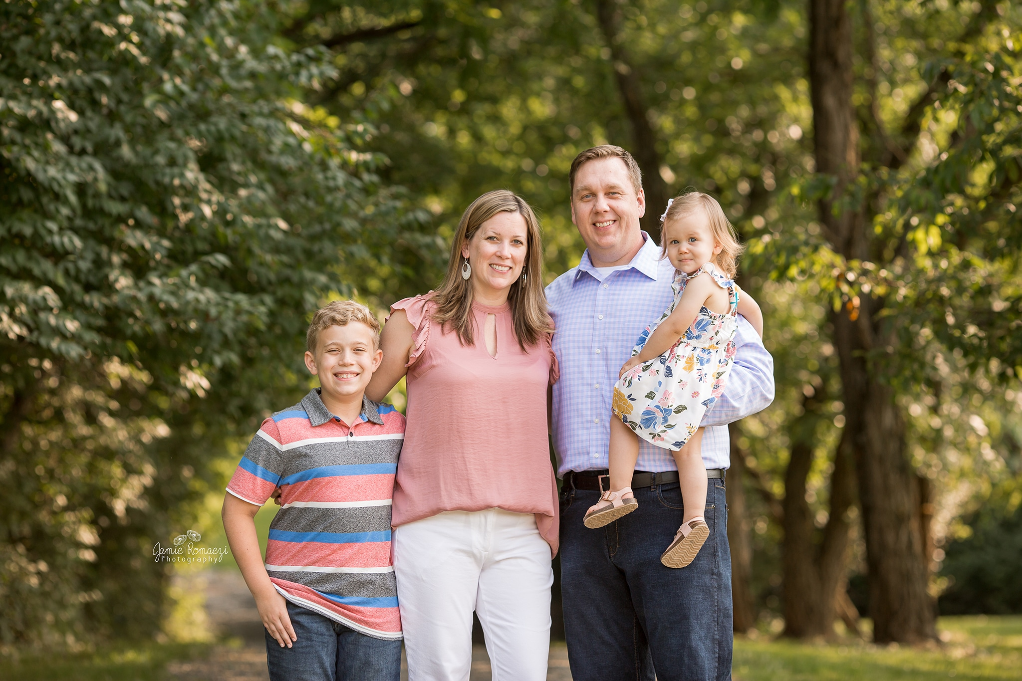 Spring family photos. Family standing on a gravel trail in front of trees.