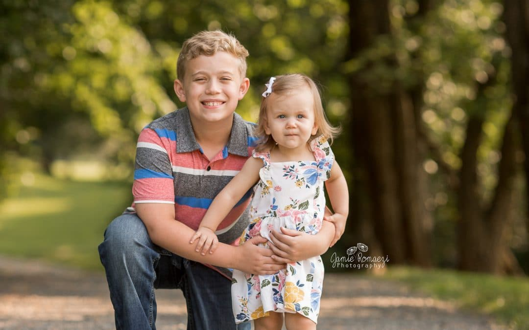 Spring portrait of big brother and little sister. Brother is kneeling with little sister on a gravel trail in front of green, leafy trees.