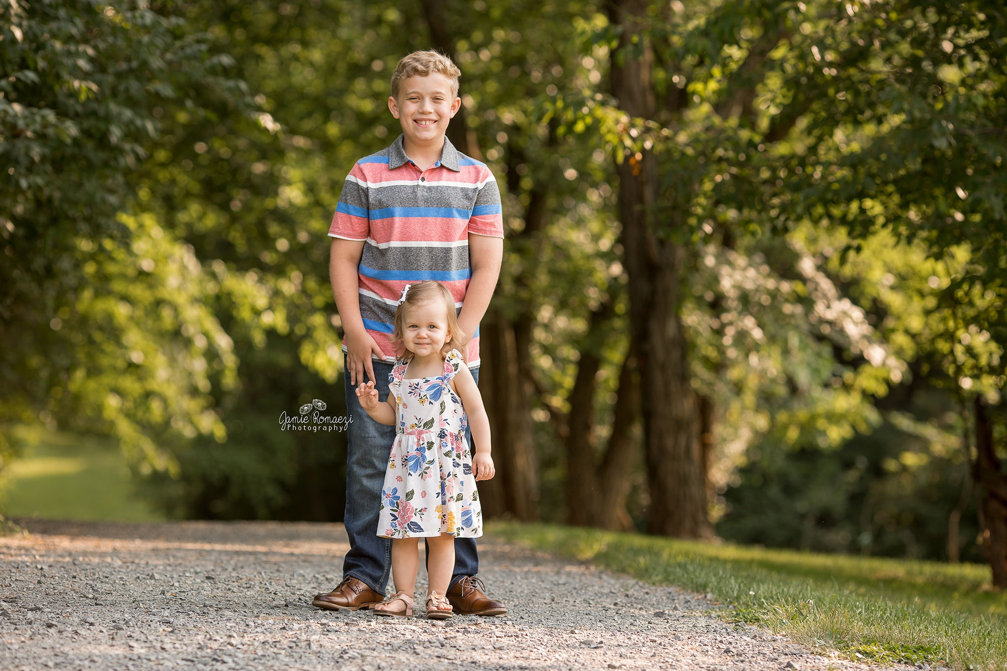 Spring portrait of big brother and little sister. Brother is holding little sister's shoulders on a gravel trail in front of green, leafy trees.
